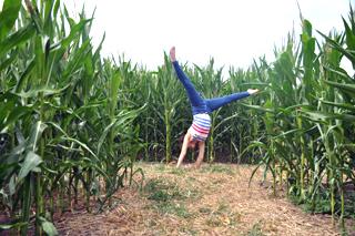 Mädchen schlägt Rad im Maislabyrinth Dalheim